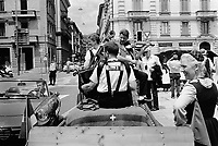 Switzerland. Canton Ticino. Lugano. Federal Choir Festival in Costume. The beauty and tradition of costumes from all regions of Switzerland. A group of musicians seat on a charriot play accordion, violin and bass. A blanked from the swiss army with a white cross. A man in a convertible car. A policeman and a private security guard are taking care of traffic. 12.06.2016 © 2016 Didier Ruef