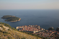 The island of Lokrum and the medieval walled city, with the defensive walls and the Minceta Tower, and the old harbour on the left, Dubrovnik, Croatia. The city developed as an important port in the 15th and 16th centuries and has had a multicultural history, allied to the Romans, Ostrogoths, Byzantines, Ancona, Hungary and the Ottomans. In 1979 the city was listed as a UNESCO World Heritage Site. Picture by Manuel Cohen