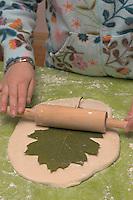 Kinder basteln Blattkacheln aus Salzteig, Mädchen macht einen Abdruck von einem Eichenblatt auf den Salzteig