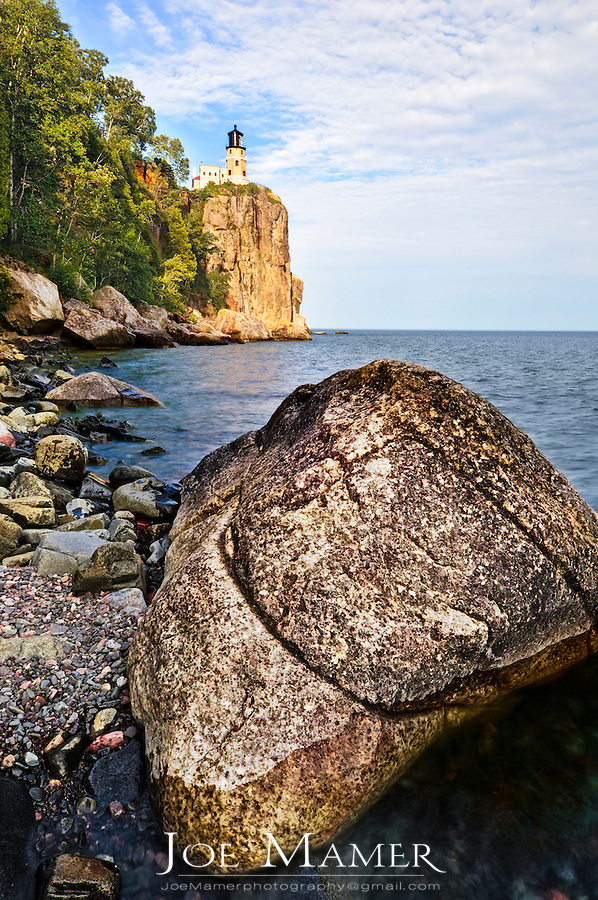 A large boulder lies on the shore of Lake Superior a short distance from Split Rock Lighthouse. Split Rock Lighthouse is located southwest of Silver Bay, Minnesota, USA on the North Shore of Lake Superior. The structure was designed by lighthouse engineer Ralph Russell Tinkham and was completed in 1910 by the United States Lighthouse Service at a cost of $75,000, including the buildings and the land. It was built in response to the loss of ships during the famous Mataafa Storm of 1905, in which 29 ships were lost on Lake Superior.[3] One of these shipwrecks, the Madeira, is located just north of the lighthouse. The light was first lit on July 31, 1910.