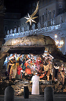 Pope Francis prays in front of a Nativity scene in St Peter's square at the Vatican.December 31,2013