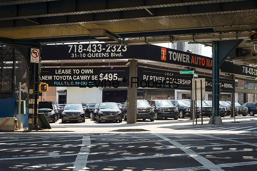 An automobile deal partners with Uber in Long Island City in the borough of Queens in New York on Sunday, June 26, 2016. According to a number of surveys Queens, particularly Western Queens with its proximity to Midtown Manhattan, is poised to become the next trendy location, supplanting Brooklyn. (© Richard B. Levine)