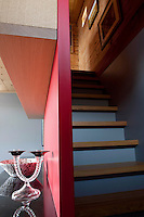 A contemporary open staircase concealed behind open shelving in the living area leads to the bedroom floor