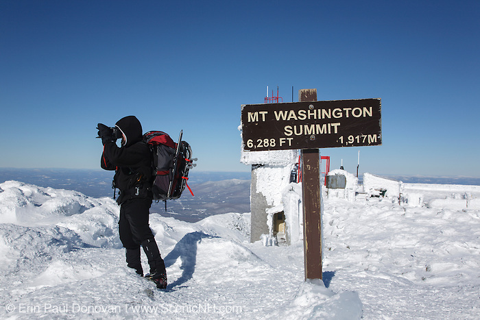 A hiker photographs around the summit of Mount Washington during the winter months in the White Mountains, New Hampshire USA