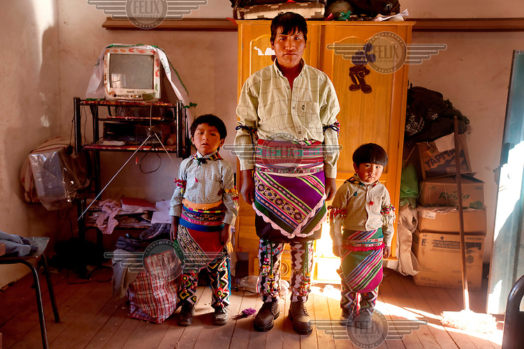 Senovio Suyo and his sons David, 6, and Ariel, 4, stand in his bedroom dressed in in traditional Tinku outfits before the fights in Macha. <br /> <br /> The people of Macha and surrounding communities carry on the pre-Columbian tradition of ritual fighting. The communities gather on the plaza of Macha to fight and dance in competition with each other. The blood that is spilled is an offering to Mother Earth. In return, the people ask for rain and a good harvest. This ritual is called tinku or fiesta de la cruz since the cross is also engaged in the festivities. The cross is dressed up, given offerings and brought from communities around Macha to the church in town. This syncretic festival melds pagan, pre-christian rituals with Catholic practice. /Felix Features
