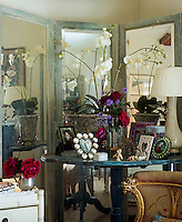 In the living room a mirrored screen has been placed behind a pedestal table laden with framed photographs and a large orchid