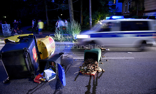 A police car drives past overturned rubbish bins during demonstrations against the G20 summit in Hamburg, Germany, 7 July 2017. The summit, a meeting of the governments of the twenty largest world economies, begins on the 7 July and concludes on the 8 July. Photo: Axel Heimken/dpa /MediaPunch ***FOR USA ONLY***