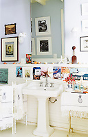 This simple bathroom is decorated with vintage magazine clippings and nautical-style sconces