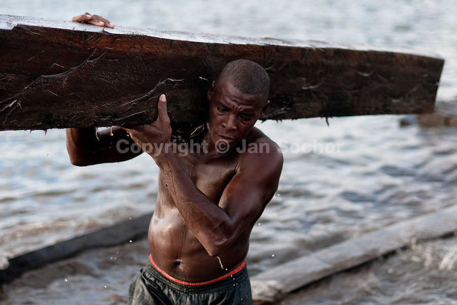 A Colombian sawmill worker carries a timber from the Pacific rainforest in Tumaco, Colombia, 15 June 2010. Tens of sawmills located on the banks of the Pacific jungle rivers generate almost half of the Colombia's wood production. The wood species processed here (sajo, machare, roble, guabo, cargadero y pacora) are mostly used in the construction industry and the paper production. Although the Pacific lush rainforest in Colombia is one of the most biodiverse area of the world, the region suffers an extensive deforestation due to the uncontrolled logging in the last years.