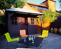 View of deck area with modern table and chairs in front of painted shed
