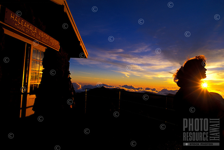 A woman views a sunrise at the Haleakala National Park Visitor Center.