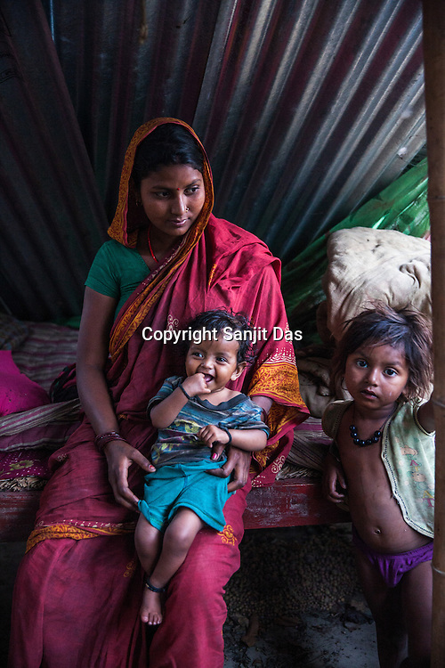 21 year old Asha Devi holds her 11 month daughter, Sita Mandal while her 3 year old son, Gaurav Mandal (left) stands next to her in their house in Bhardaha in Saptari, Nepal.