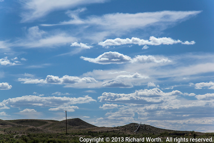 There is a little black dot in an otherwise pristine sky of clouds and blue.  It is a bird - crow, raven or blackbird- but it is not a speck of dirt on a lens, and so, it remains.  Clouds over high desert fence in Wyoming at Fort Steele, near Rawlins.