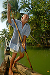 Indian boatman with a punt pole on a boat in the backwaters. Kerala, India.