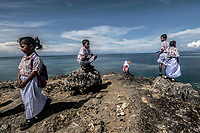 Bajau schoolchildren look out to sea during a break from class in the village of Kabalutan in the Togean Islands.