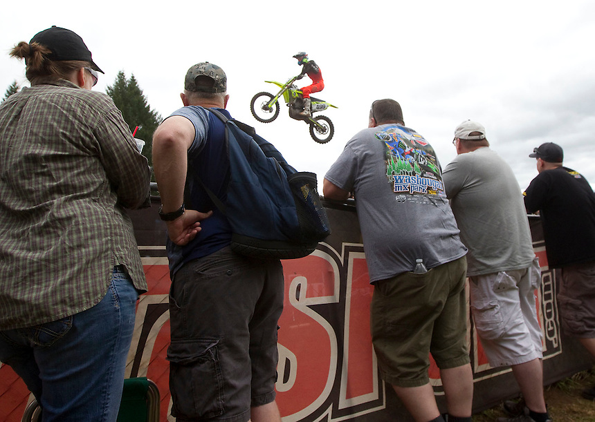 A motorcycle flies over the heads of spectators at the Washougal MX National in Washougal Saturday July 23, 2016. D(Photo by Natalie Behring/ for the The Columbian)