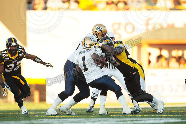Aug 3, 2007; Hamilton, ON, CAN; Hamilton Tiger-Cats defensive end (99) Jermaine Reid tackles Winnipeg Blue Bombers running back (1) Charles Roberts during the first quarter at Ivor Wynne Stadium. The Tiger-Cats defeated the Blue Bombers 43-22. Mandatory Credit: Ron Scheffler.