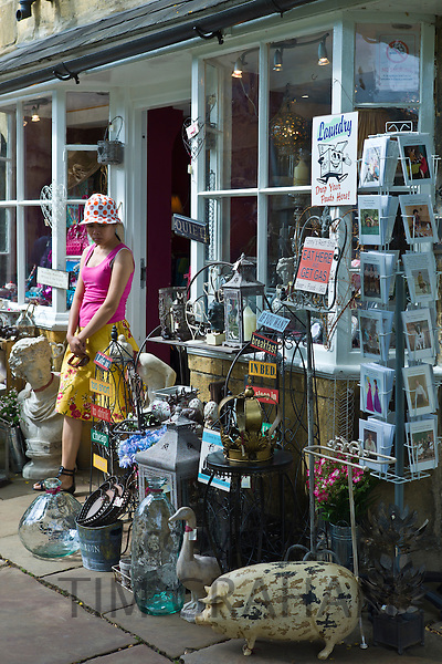 Tourist leaving curiosity shop selling souvenirs, collectibles and gift items in Chipping Campden, The Cotswolds, UK