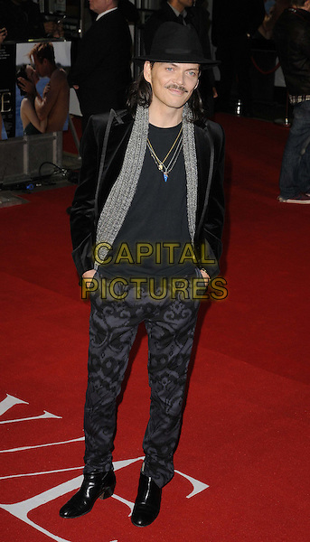 Matthew Williamson.W.E. UK film premiere at Odeon cinema, Kensington, London, England..11th January 2011.full length black suit jacket hat grey gray scarf trousers pattern print hands in pockets.CAP/CAN.©Can Nguyen/Capital Pictures.