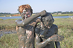 Children covered from head to toe in mud playing in pools of the Butley Creek river estuary, Suffolk, England, UK - no MR