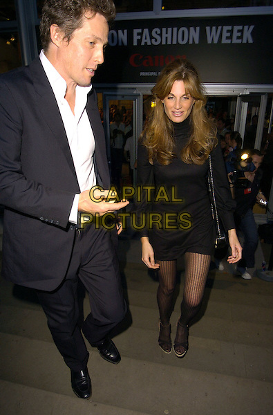 HUGH GRANT & JEMIMA KHAN .At the BIBA Spring/Summer 2007 Catwalk Show during London Fashion Week, BFc Tent, Natural Hitsory Museum, London, England, September 19th 2006..full length goldsmith suit jacket white shirt black dress patterned tights walking up steps stairs hand.Ref: CAN.www.capitalpictures.com.sales@capitalpictures.com.©Can Nguyen/Capital Pictures
