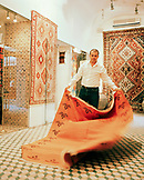 TURKEY, Istanbul, mid adult man holding Turkish carpet in his store in the Grand Bazaar.