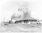 D&amp;RGW #489 with eastbound coal train approaching Gunnison depot.  1955 Buick and 1953-1955 International pickup parked by the depot.<br /> D&amp;RGW  Gunnison, CO  Taken by Krause, John - early 1950-1952