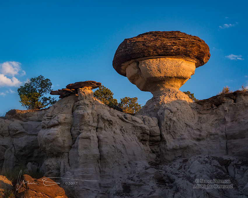 Sunrise Mushroom, Northwest New Mexico ©2017 James D Peterson.  A sandstone cap rock, protecting its mudstone base from erosion, forms a mushroom hoodoo in this rugged badlands area.