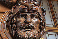 Sculpted wooden head of man wearing lion's head helmet, possibly Heracles, from the door between the horseshoe vestibule and the Galerie Francois I, Chateau de Fontainebleau, France. The Galerie Francois I was begun in 1528 and was the first great gallery in France and the origination of the Renaissance style in France. The Palace of Fontainebleau is one of the largest French royal palaces and was begun in the early 16th century for Francois I. It was listed as a UNESCO World Heritage Site in 1981. Picture by Manuel Cohen