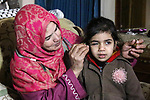 "A Palestinian woman Hadia Qudaih 70, puts a traditional eye cosmetic ""Arab kohl or Black eyeliner"" in the eye of a girl at her home in Khan Younis in the southern of Gaza strip, on February 17, 2020. Eye liner or eyeliner is a cosmetic used to define the eyes. It is applied around the contours of the eye(s) to create a variety of aesthetic effects. The history of cosmetics traverse from at least 7,000 years and is common in mostly every society. Photo by Mariam Dagga"