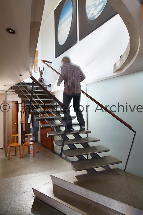 The back view of a man climbing an elegant, contemporary staircase, which seems to defy gravity in a spacious entrance hall.