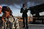 Opposition rebels reload ammunition near an oil refinery in Ras Lanuf, Libya, March, 11, 2011. Loyalist forces of Col. Muammar Qaddafi pushed rebels back from the strategic oil town with air strikes, artillery and small arms fire.