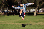 Authentic action of happy boy running and jumping in the park - with copy space to sides