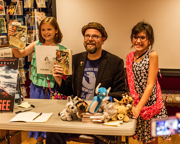 July 26, 2017. Raleigh, North Carolina.<br /> <br /> Alan Gratz poses for a photo with (L to R) Nina Macleod and Skyler Game. They both came dressed up as Hachi, a character form Gratz's League of Seven Characters series. <br /> <br /> Author Alan Gratz spoke about and signed his new book &quot;Refugee&quot; at Quail Ridge Books. The young adult fiction novel contrasts the stories of three refugees from different time periods, a Jewish boy in 1930's Germany , a Cuban girl in 1994 and a Syrian boy in 2015.