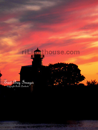 A blazing sun sets behind the Pomham Rocks Lighthouse.