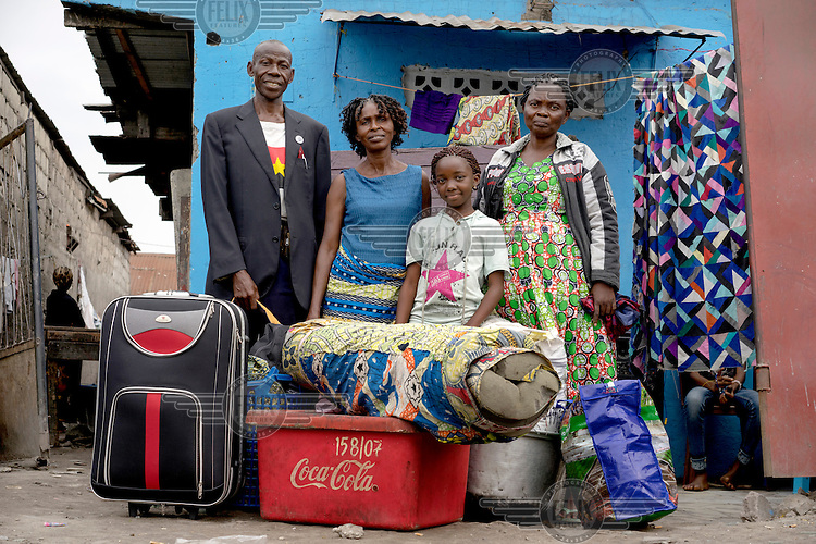 From left, former Angolan refugees Antonio Tama, b. 1948, his sister Maria Mafuta, b. 1953, orphaned granddaughter Faria Larite, b. 2003, and wife Albertine Conde, b. 1954, pose for a portrait with their luggage in front of the house they have been renting in Kinshasa. The family, along with nearly 500 other former refugees, departed Kinshasa to return to Angola on 19 August, 2014.  The journey, made on train and bus, took approximately 36 hours to reach the Angolan border. The UNHCR is coordinating the return of nearly 30,000 former refugees to Angola.