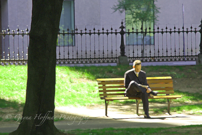 Man sitting on a park bench in the sun, legged crossed.