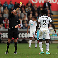 Referee Lee Mason shows a yellow card to Wilfried Bony of Swansea City during the Premier League match between Swansea City and Watford at The Liberty Stadium, Swansea, Wales, UK. Saturday 23 September 2017
