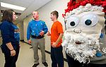 SOUTHBURY, CT-122117JS06---Stephanie Bergman, a special education teacher at Pomperaug High School in Southbury, left, talks with special education teacher Mike Giordano and life skills program student Nick Mattson, right, as school councilor Carol Reilly, right, shows off her Santa sweater during the annual Holiday Sweater Contest at the school on Thursday. Students with the LINK Crew and the Life Skills Program created the holiday themed shirts for teachers in the school. Students then vote for their favorite by donating a dollar per vote. Money raised from the even will be donated to the Vicky Soto Memorial Fund. <br /> Jim Shannon Republican-American