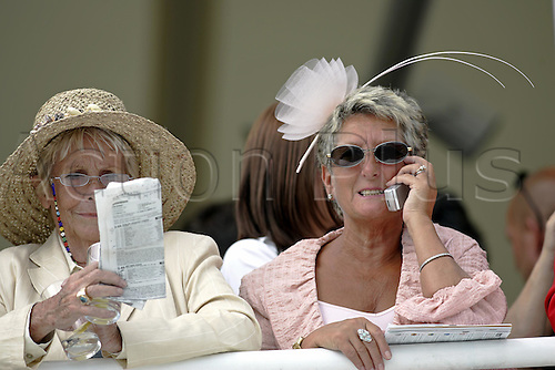 27 July 2004: Two Ladies at Goodwood Photo: Glyn Kirk/Action Plus...horse racing 040727 hat fashion telephone race card glorious women