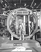 Astronaut John H. Glenn Jr., suited with hose to suit ventilation unit attached, during altitude chamber test in 1961. He is standing in the entrance to the test chamber with his helmet visor down..Credit: NASA via CNP