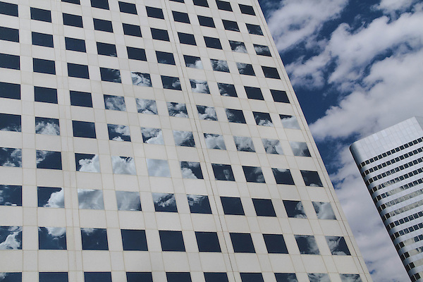 Glass and metal building reflecting the sky, along the 16th Street Mall in downtown Denver, Colorado, USA .  John offers private photo tours in Denver, Boulder and throughout Colorado. Year-round Colorado photo tours.