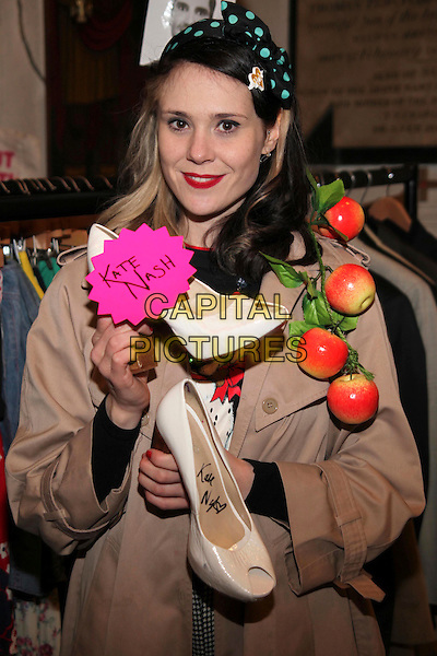 Kate Nash.Celebrity jumble sale in aid of Oxfam, London, England..February 26th, 2012.half length shoes black blue polka dot bow in hair beige jacket apples .CAP/JEZ  .©Jez/Capital Pictures.