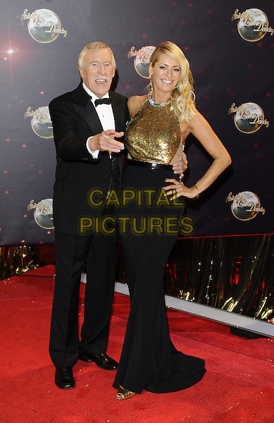 Bruce Forsyth &amp; Tess Daly<br /> The red carpet launch for 'Strictly Come Dancing' at Elstree Studios, Borehamwood, England.<br /> September 3rd, 2013<br /> full length gold sleeveless sequins sequined black skirt top dress hand on hip tuxedo  hand finger pointing <br /> CAP/FIN<br /> &copy;Steve Finn/Capital Pictures