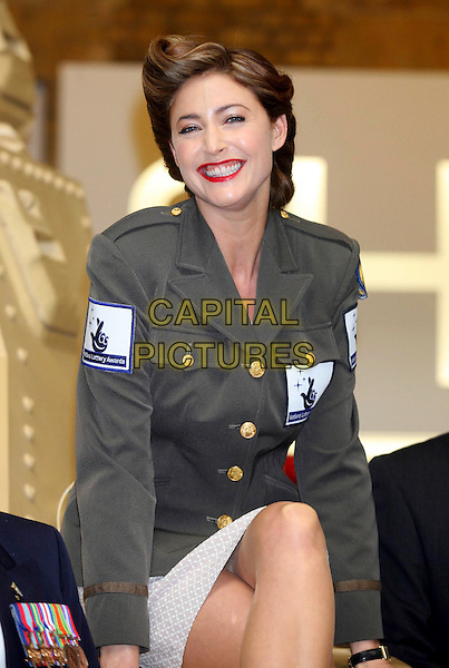 LISA SNOWDON.joined war veterans to launch The National Lottery Awards 2009 at The Imperial War Museum, London, England, February 11th 2009..half length forties style hair up smiling uniform green military jacket legs crossed skirt sitting red lipstick .CAP/DS.©Dudley Smith/Capital Pictures