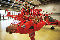 "Switzerland. Canton Ticino. Locarno Airport LSZL. The Rega base's official name is Locarno LSMO AFB (Rega 6). By using a rescue hoist, a helicopter can rescue persons from hard-to-reach areas in the Alps. Once a month, the emergency doctors working for Rega have to train the various winch evacuation proceedings. In order to get their flying clearances, they need to pass the test successfully. The physician Michele Musiari (C) is exercising an evacuation with a patient lying in a horizontal net. The net is used with patients injured with serious backs problems. The Rega pilot Corrado Sasselli plays the role of the patient. In the background, a Rega Agusta AW109 SP Grand ""Da Vinci"" helicopter. All Rega helicopters carry a crew of three: a pilot, an emergency physician, and a paramedic who is also trained to assist the pilot for radio communication, navigation, terrain/object avoidance, and winch operations. The name Rega was created by combining letters from the name ""Swiss Air Rescue Guard"" as it was written in German (Schweizerische Rettungsflugwacht), French (Garde Aérienne Suisse de Sauvetage), and Italian (Guardia Aerea Svizzera di Soccorso). Rega is a private, non-profit air rescue service that provides emergency medical assistance in Switzerland. Rega mainly assists with mountain rescues, though it will also operate in other terrains when needed, most notably during life-threatening emergencies. As a non-profit foundation, Rega does not receive financial assistance from any government. The AgustaWestland AW109 is a lightweight, twin-engine, helicopter built by the Italian manufacturer Leonardo S.p.A. (formerly AgustaWestland, Leonardo-Finmeccanica and Finmeccanica). Leonardo S.p.A is an Italian global high-tech company and one of the key players in aerospace. In close collaboration with the manufacturer, the Da Vinci has been specially designed to cater for Rega's particular requirements as regards carrying out operations in the mountains. It optimally fulfil"