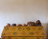 A row of dainty silk hats is displayed on a hand-painted bureau