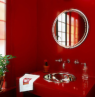 The all red guest bathroom has a chrome basin and taps and a round mirror