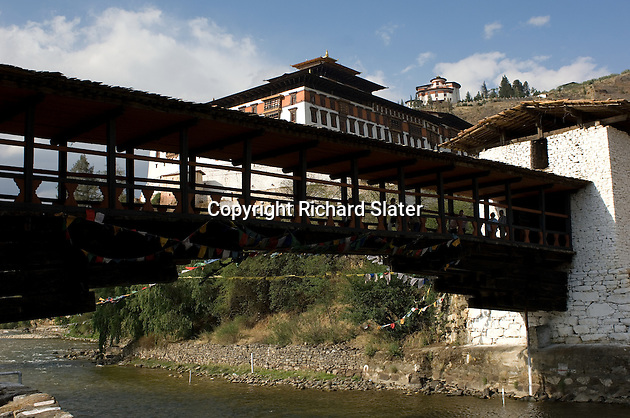 The traditional covered wooden bridge which crosses the river at Paro, Bhutan, to the Rinpung Dzong (literally the fortress of the heap of jewels). The National Museum is visible further up the hill.
