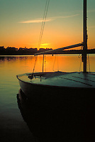 Sailboat on lake at sunset.